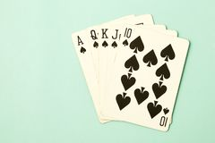 Royal flush poker cards combination. Royal straight flush playing cards poker hand in spades blue pastel background Royalty Free Stock Photo