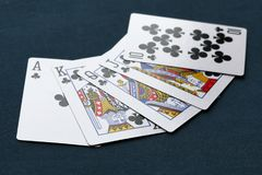 Royal flush poker hand of clubs on a dark background. Royal flush poker hand of clubs on a dark blue grungy background Royalty Free Stock Image