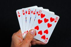 Royal flush poker hand. Royakl flush poker hand in the heart suit against a black background stock images