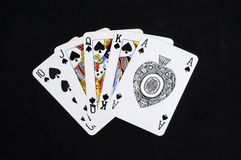Royal flush poker hand. Royal Flush poker hand in the spade suit against a black background Royalty Free Stock Photo