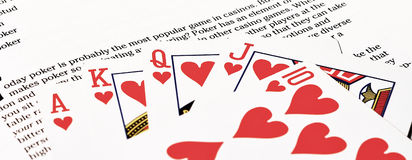 Royal flush poker text. Shot of a royal flush on top of a book that talks about poker Royalty Free Stock Photo