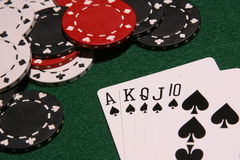 Royal flush spades. Hand of playing cards making a royal flush and poker chips Stock Image