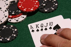 Royal flush spades. Hand of poker cards making a royal flush in spades with poker chips Stock Images