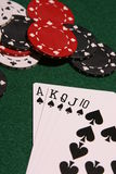 Royal flush spades casino chips. Playing cards with a royal flush in spades and a pile of casino chips Stock Photos