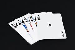 Royal Flush von Spaten im PokerKartenspiel auf einem schwarzen Hintergrund lizenzfreies stockfoto