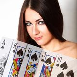 Royal flush. The woman got the best combination in poker. The peak royal flush. Beautiful eyes Royalty Free Stock Photos