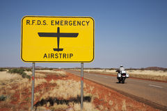Royal Flying Doctor Sign Outback Australia. Sign for Royal Flying Doctor Service emergency runway (on the road) in outback Western Australia, motor cyclist just Royalty Free Stock Images