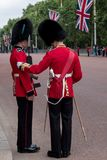 Royal Guard soldier in red and black uniform with bearskin hat stands to attention while colleague inspects him. The Mall, London royalty free stock photography