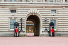 Royal Guards at Buckingham Palace. The Royal Guards dressed in their traditional unforms standing at the gates of Buckingham Palace in London Stock Photography