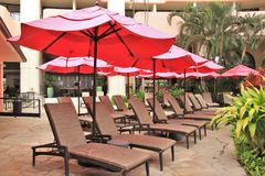 Royal Hawaiian Hotel, Honolulu, Hawaii -4/27/2018 - Lounge chairs and umbrellas by the pool at the Royal Hawaiian Hotel in Hawaii. Poolside area at the Royal stock photo