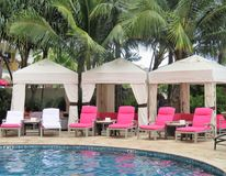 Royal Hawaiian Hotel, Honolulu, Hawaii -4/27/2018 - Lounge chairs and umbrellas by the pool at the Royal Hawaiian Hotel in Hawaii. Poolside area at the Royal stock images