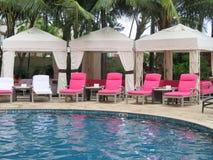 Royal Hawaiian Hotel, Honolulu, Hawaii -4/27/2018 - Lounge chairs and umbrellas by the pool at the Royal Hawaiian Hotel in Hawaii. Poolside area at the Royal royalty free stock photo