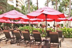 Royal Hawaiian Hotel, Honolulu, Hawaii -4/27/2018 - Lounge chairs and umbrellas by the pool at the Royal Hawaiian Hotel in Hawaii. Poolside area at the Royal royalty free stock images