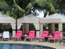 Royal Hawaiian Hotel, Honolulu, Hawaii -4/27/2018 - Lounge chairs and umbrellas by the pool at the Royal Hawaiian Hotel in Hawaii. Poolside area at the Royal royalty free stock image