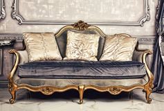 Royal interior, sofa, Living room, antique, stylish, luxurious,. Royal interior. Living room with an antique stylish light sofa with luxurious gold accessories royalty free stock images