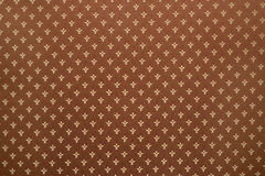 Royal lily or fleur-de-lis pattern on cloth. Brown textile background with royal lily or fleur-de-lis pattern on cloth texture Royalty Free Stock Images