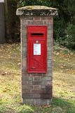 A royal mail post box in a brick pillar on the green. stock image