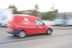 Royal Mail van blurred and in motion. A blurred image of a Royal Mail van driving along an urban road Stock Images