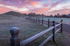 Royal mounds. Sunrise view of the King's graves and protecting fences in Gamla Uppsala, Sweden stock image