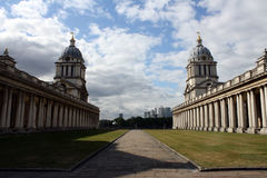 Royal Naval College Greenwich in London. It faces the Thames. On the horizon are the buildings of Canary Wharf Royalty Free Stock Photo