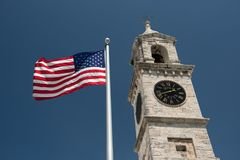 Royal Naval Dockyard Clock Tower in Bermuda. The United States flag flying in the breeze adjacent to the Clock Tower at the Royal Naval Dockyard in St. George stock photos