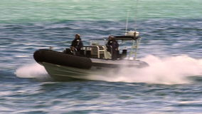 Royal New Zealand navy sailors ride a Zodiak boat. Royal New Zealand navy sailors ride a Zodiak Rigid-hulled inflatable boat in ports of Auckland.The RNZN has a stock video