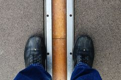 Feet astride the Prime Meridian line in Greenwich. At the Royal Observatory in Greenwich, England, the Prime Meridian Line which marks zero degrees longitude on Stock Photos