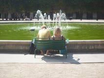 Royal Palace, Paris, França, o 17 de agosto de 2018: acople o assento em uma cadeira dobro na frente de uma fonte imagens de stock