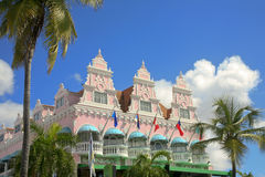 The Royal Plaza, Oranjestad, Aruba. The iconic pink Royal Plaza in central Oranjestad, Abruba. The building has six balconies with aqua covers. Four flags are at Royalty Free Stock Images