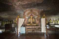 Into the Royal Rock Temple, Dambulla, Sri Lanka. Royal Rock Temple, paintings, frescoes and sculptures of Buddha, sitting Buddha in Buddhist temple excavated in stock image