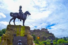 The Royal Scots Greys Monument in Princes Street with Princes St. Reet Gardens and Edinburgh Castle at background, in Edinburgh, Scotland Royalty Free Stock Image