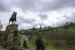 Royal Scots Greys statue,  Princes Street Gardens. Edinburgh Castle, back ground. Edinburgh, Scotland Royalty Free Stock Photography