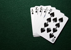 Royal straight in spades. A view of playing cards in a royal straight flush in spades on a green felt background Royalty Free Stock Photography