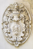 Royal symbols. Emblem with royal symbols in bas-relief on a wall Stock Photos