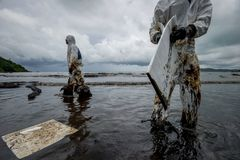 Royal Thai Navy and local volunteers cleaning up a beach from a oil slick on Ao Phrao beach on Samed Island, rayong, Thailand. An. Oil leak from a pipeline royalty free stock image