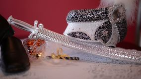 Royal turban, decorative saber and shoe on the bed
