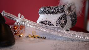 Royal turban, decorative saber and shoes on the bed