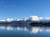 Roys bay at Wanaka in New Zealand with snow capped mountains and clouds in view. Roys bay at Wanaka with snow capped mountains and clouds in view royalty free stock images