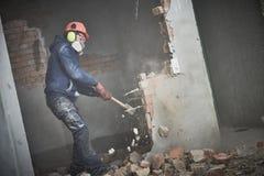 Rozbiórkowa praca i prześciełanie pracownik z młotem niszczy ścianę obrazy royalty free