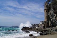 Rozbijać macha na skalistej plaży z małym wiktoriański kasztelem na stronie faleza Fotografia Royalty Free