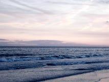 Rozbijać na plaży przy zmierzchem Zdjęcia Royalty Free