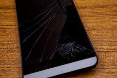 Rozbijający telefon komórkowy na stole Czarny telefon komórkowy na drewnianym stole z rozbijającym lcd pokazem Mobilny technologi Obrazy Royalty Free