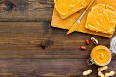 Rozciągnięty dokrętki masło na kanapce Grzanka, nóż i szklany słój z dokrętki pastą, dokrętki na ciemnej drewnianej tło kopii prz Zdjęcia Royalty Free