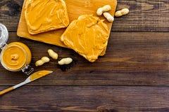 Rozciągnięty dokrętki masło na kanapce Grzanka, nóż i szklany słój z dokrętki pastą, dokrętki na ciemnej drewnianej tło kopii prz Obrazy Stock