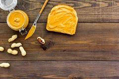 Rozciągnięty dokrętki masło na kanapce Grzanka, nóż i szklany słój z dokrętki pastą, dokrętki na ciemnej drewnianej tło kopii prz Zdjęcie Stock