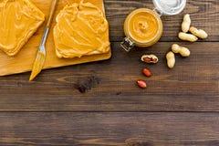 Rozciągnięty dokrętki masło na kanapce Grzanka, nóż i szklany słój z dokrętki pastą, dokrętki na ciemnej drewnianej tło kopii prz Obraz Stock