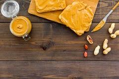 Rozciągnięty dokrętki masło na kanapce Grzanka, nóż i szklany słój z dokrętki pastą, dokrętki na ciemnej drewnianej tło kopii prz Fotografia Stock