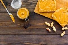 Rozciągnięty dokrętki masło na kanapce Grzanka, nóż i szklany słój z dokrętki pastą, dokrętki na ciemnej drewnianej tło kopii prz Zdjęcia Stock