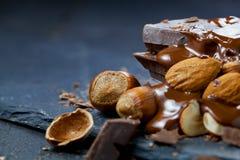 Rozciekły czekoladowy dolewanie w kawałek czekoladowi bary na stole zdjęcia stock