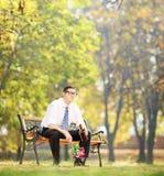 Rozczarowana mężczyzna mienia butelka gorzała w parku obrazy stock